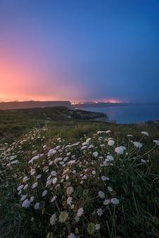 Paysage côtier la nuit avec des couleurs chaudes et froides dans un ciel nuageux