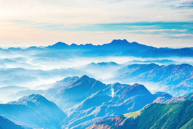 Paysage avec coucher de soleil dans les montagnes bleues et le brouillard