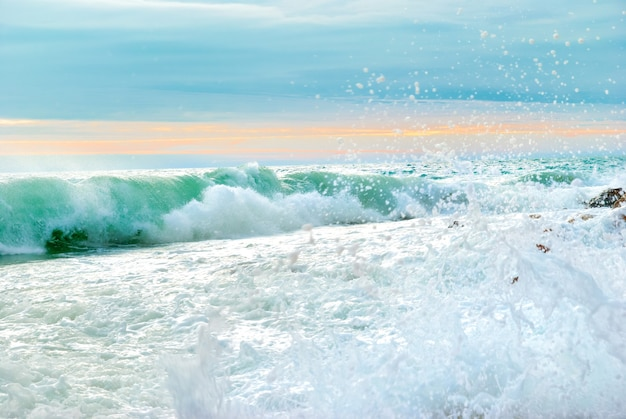 Paysage de coucher de soleil sur la mer avec de grosses vagues écrasant le rivage