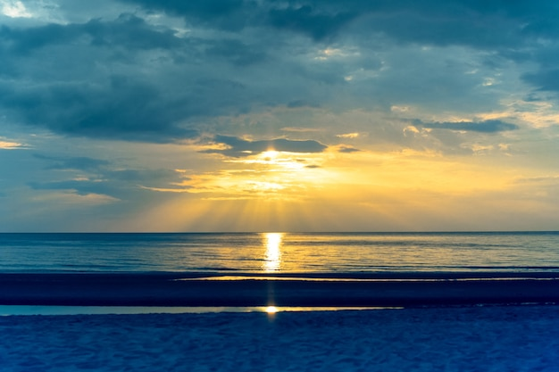 Paysage coucher de soleil sur la plage avec des reflets légers sur l'océan en couleurs croisées.