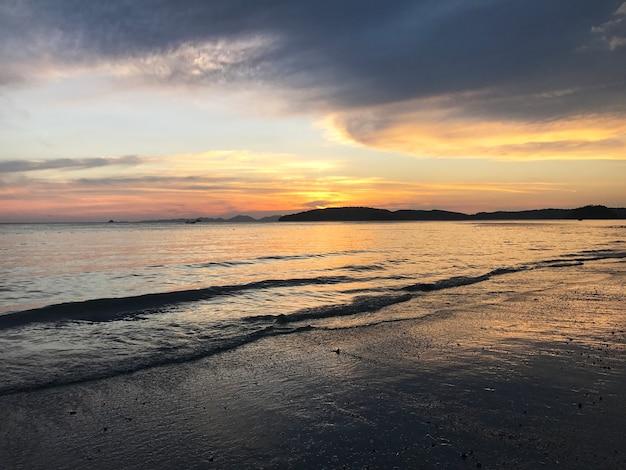 Paysage de coucher de soleil, de sable et de vagues sur la plage