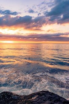 Paysage à couper le souffle d'une plage rocheuse sur un beau fond de coucher de soleil