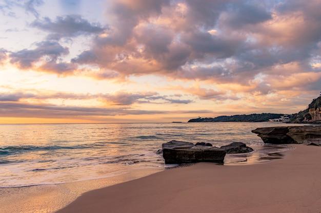 Paysage à couper le souffle d'une plage rocheuse sur un magnifique coucher de soleil
