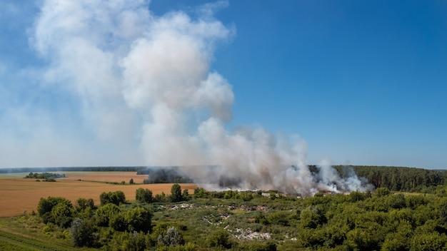 Paysage de dépotoir brûlant dans la campagne. problème de pollution écologique