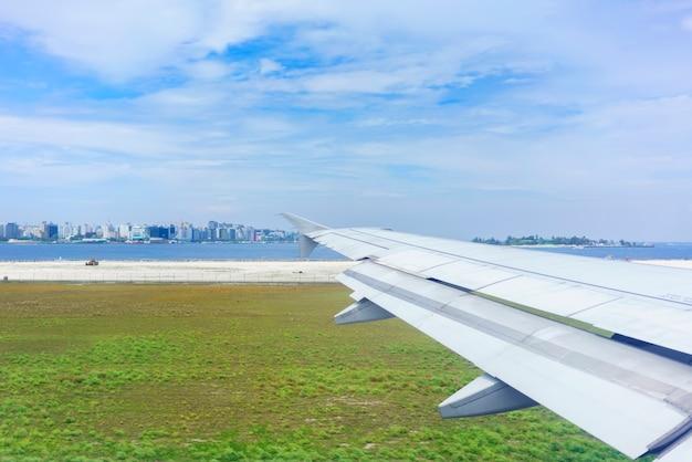 Paysage depuis la fenêtre de l'avion après l'atterrissage , voyant l'aile de l'avion et malé , capitale de la république des maldives située dans l'océan indien