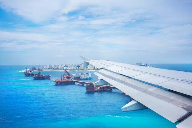 Paysage depuis la fenêtre de l'avion avant l'atterrissage , voyant l'aile de l'avion et malé , capitale de la république des maldives située dans l'océan indien