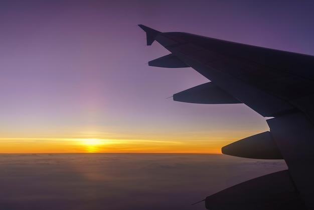 Paysage depuis la fenêtre de l'avion avec vue sur l'aile de l'avion et le beau coucher de soleil