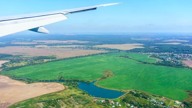 Paysage depuis la fenêtre de l'avion avec vue sur l'aile de l'avion, ciel bleu clair et paysage de moscou, russie
