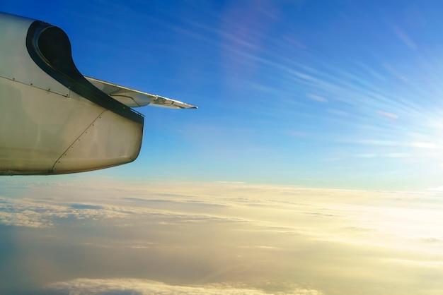 Paysage depuis la fenêtre de l'avion avec vue sur l'aile de l'avion et les nuages dorés et le ciel bleu le matin