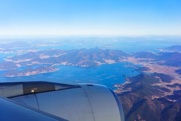 Paysage depuis la fenêtre de l'avion avec vue sur le ciel bleu , la péninsule sud-coréenne , les îles adjacentes et la ville métropolitaine de busan le matin , corée du sud