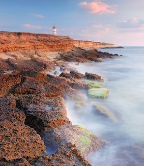 Paysage du matin sur la mer avec phare sur la côte