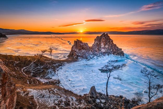Paysage du rocher shamanka au coucher du soleil avec glace naturelle dans l'eau gelée sur le lac baïkal, sibérie, russie.