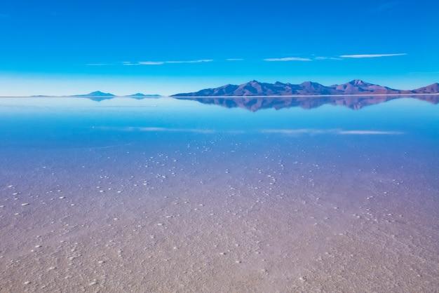 Paysage du salar de uyuni en bolivie recouvert d'eau, désert de sel et reflets du ciel