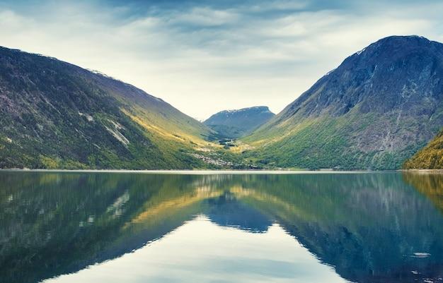 Paysage du soir du fjord de norvège dans le calme avec reflet des montagnes et du ciel dans l'eau calme en journée d'automne