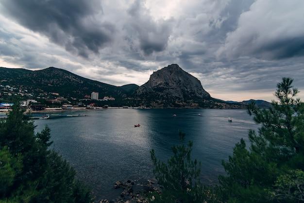 Paysage du soir nuageux de la mer et des montagnes avec la ville