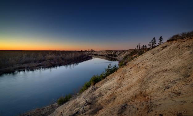 Paysage du soir avec une rivière, au coucher du soleil