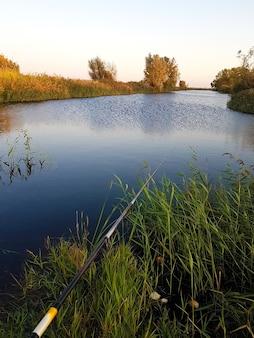 Paysage du soir à la rivière et canne à pêche