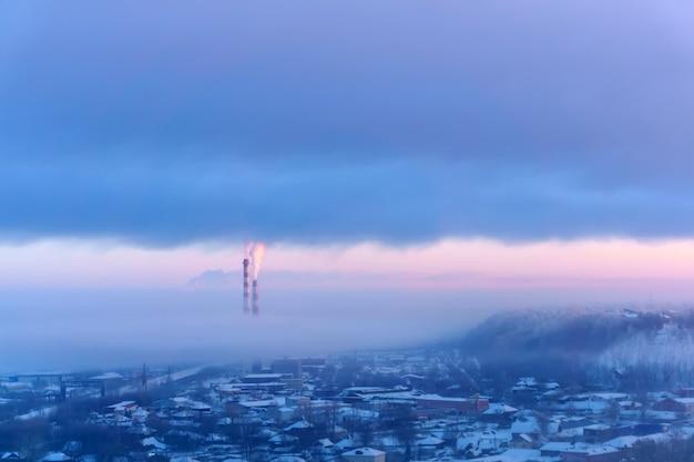 Paysage du soir d'une zone industrielle d'hiver avec cheminées fumantes et brume givrée
