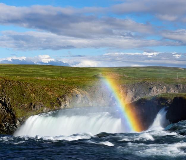 Paysage d'été avec une cascade et arc-en-ciel en islande