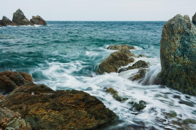 Paysage d'été de la mer avec des vagues floues, des rochers sur la plage.