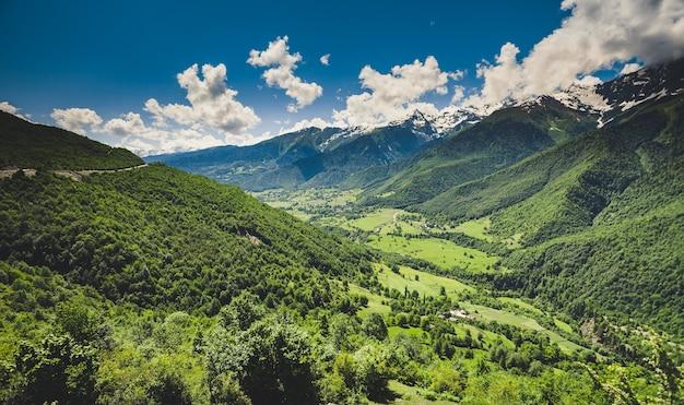 Paysage d'été panoramique avec colline verte et pic enneigé de montagne contre un ciel bleu nuageux. région de svanétie, géorgie. crête principale du caucase. fond naturel. vacances, randonnée, voyage, loisirs
