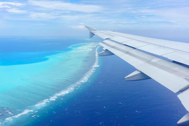Paysage de la fenêtre de l'avion voyant l'aile de l'avion nuages blancs ciel bleu îles maldives