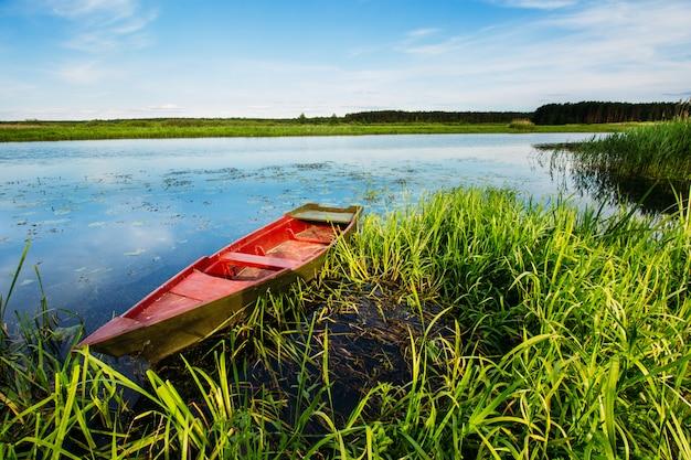 Paysage fluvial avec un bateau rouge