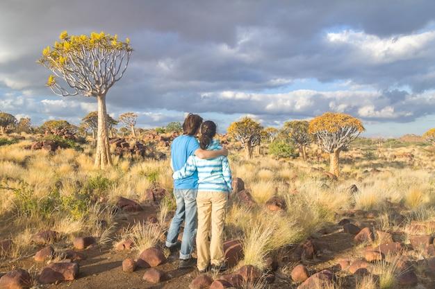 Paysage de forêt d'arbre carquois, couple de touristes regardant belle vue. kokerbooms en namibie, afrique du sud. nature africaine