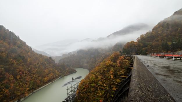 Paysage de forêt d'automne avec vue sur la vallée de la montagne brumeuse et le barrage de la rivière électrique au japon