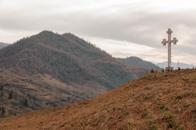 Paysage géorgien d'automne de hautes montagnes et collines avec un monument en forme de croix
