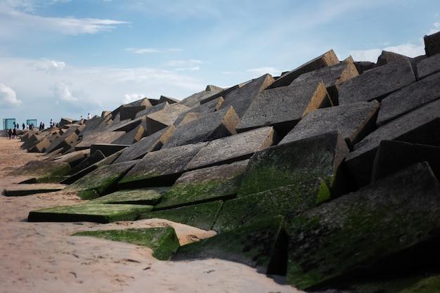 Paysage de gros cubes lapidés au bord de la mer.