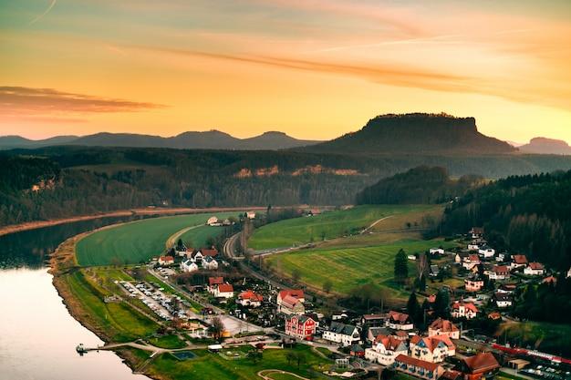 Paysage d'une hauteur d'un village allemand dans les montagnes avec vue sur la rivière et les collines au coucher du soleil