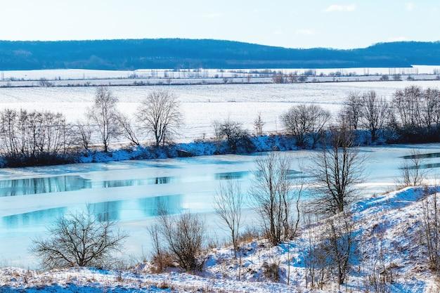 Paysage d'hiver avec des arbres au bord de la rivière et sur le terrain par une journée ensoleillée