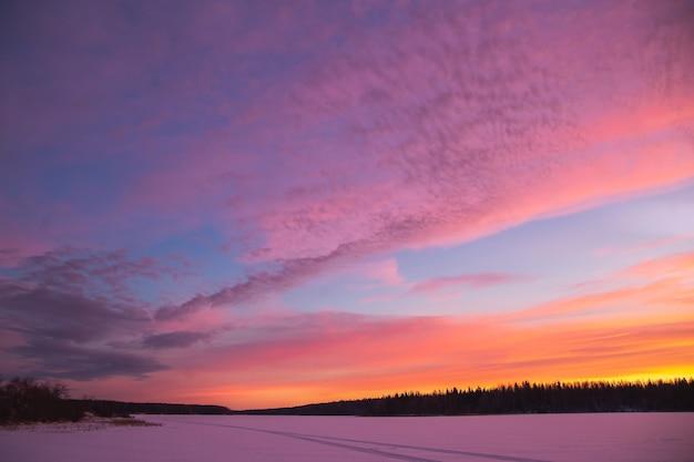 Paysage d'hiver au coucher du soleil avec route couverte de neige dans des couleurs violettes et roses