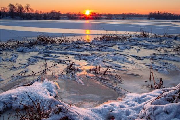 Paysage d'hiver au lever du soleil avec rive de la rivière enneigée et herbe gelée recouverte de neige au premier plan et une rivière avec de la glace scintillante reflétant le soleil