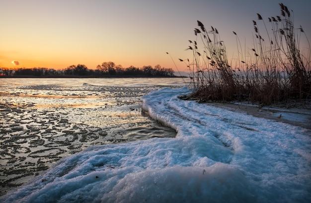 Paysage d'hiver avec ciel coucher de soleil et rivière gelée. aube