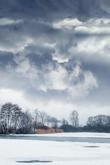 Paysage d'hiver avec un ciel nuageux dramatique au-dessus de la rivière