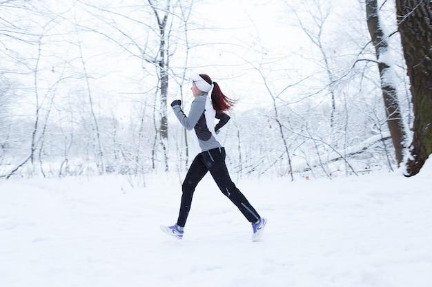 Paysage d'hiver avec une fille en cours d'exécution