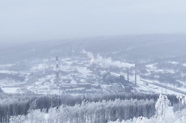 Paysage d'hiver glacial une usine métallurgique lointaine dans une vallée boisée enneigée dans une brume givrée