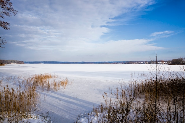 Paysage d'hiver avec lac couvert de neige et forêt mixte avec arbres feuillus et conifères après les chutes de neige et le gel, branches couvertes de neige et de glace, temps d'hiver glacial