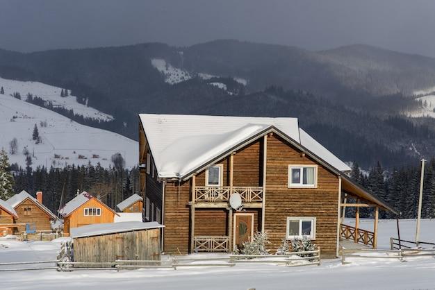 Paysage d'hiver avec maison en bois dans les montagnes enneigées