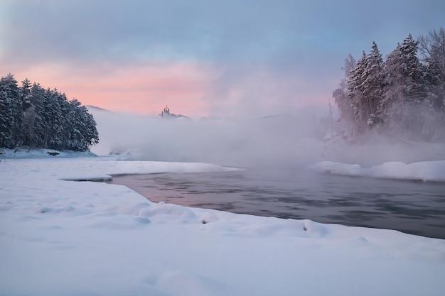 Paysage d'hiver avec une maison debout sur la rive d'une rivière gelée à bas.