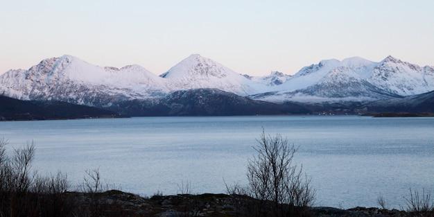 Paysage d'hiver avec des montagnes couvertes de neige à côté d'un lac gelé