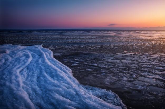Paysage d'hiver naturel au bord de la mer au coucher du soleil. ciel de glace et coucher de soleil.