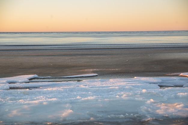Paysage d'hiver en plage, littoral avec glace fissurée et eau de mer ouverte.