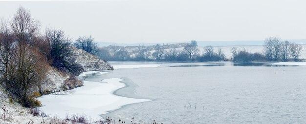 Paysage d'hiver avec rivière et arbres au bord de la rivière par temps nuageux