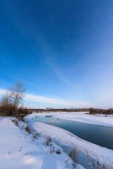 Paysage d'hiver. la rivière n'a pas gelé complètement.