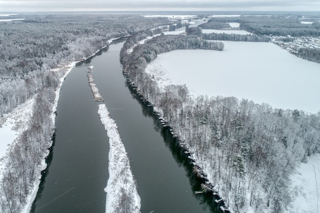 Paysage d'hiver avec une rivière qui traverse la forêt d'hiver.