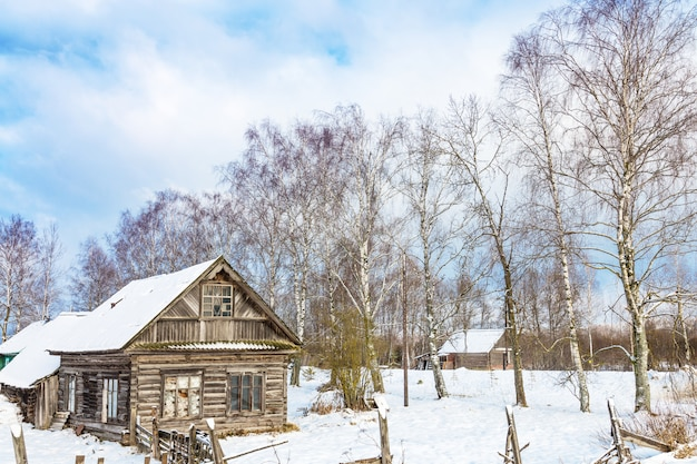 Paysage d'hiver avec une vieille maison en bois et des arbres avec un ciel bleu nuageux,