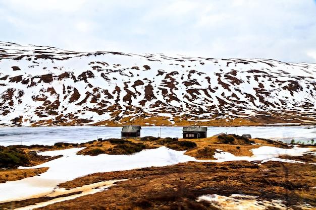 Le paysage hivernal : maisons, rivière et montagne